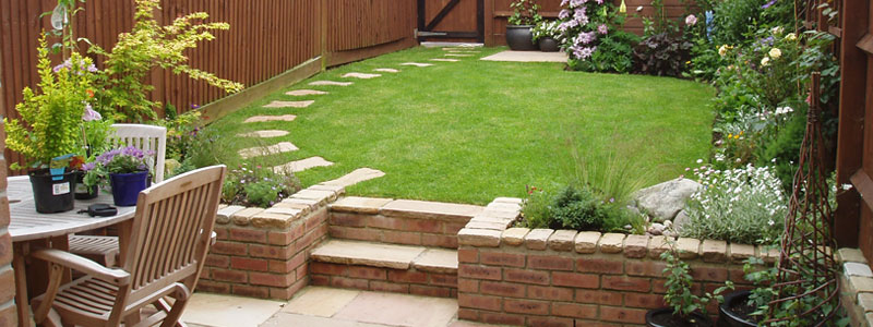 Raised grass area with tiled patio in Poole