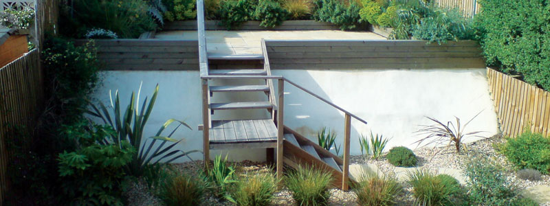 Raised back area of tropical style garden with wooden stair case and stone chip bedding